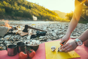 Healthy Eating While Camping - Chopping Veggies by a Rocky River